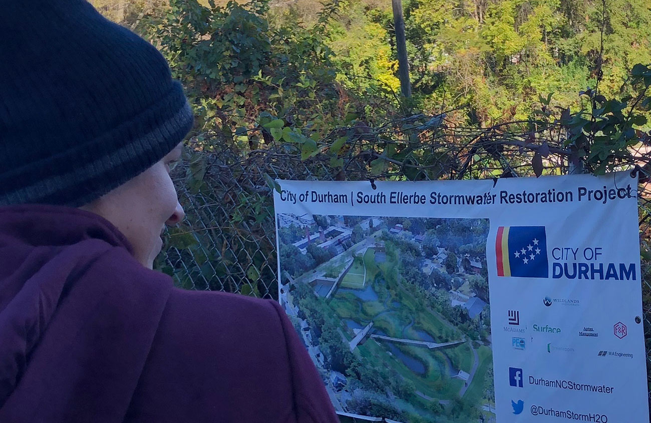 A Woman Looks at a Sign from the City of Durham about the South Ellerbe Stormwater Restoration Project